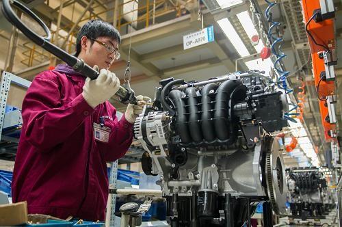 一名技术工人在江淮汽车发动机公司的总装线上组装发动机
